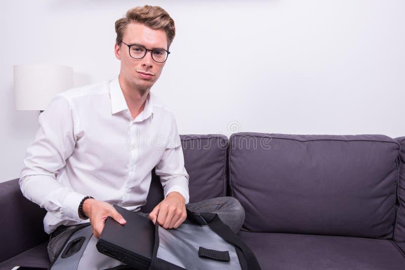 Νέο επιχειρησιακό άτομο που συσκευάζει την τσάντα του στον καναπέ στοκ φωτογραφίες
