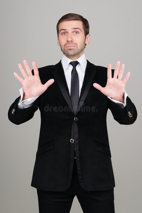 Νέο επιχειρησιακό άτομο στο μαύρο κοστούμι που κάνει την ήρεμη κάτω χειρονομία στοκ εικόνες