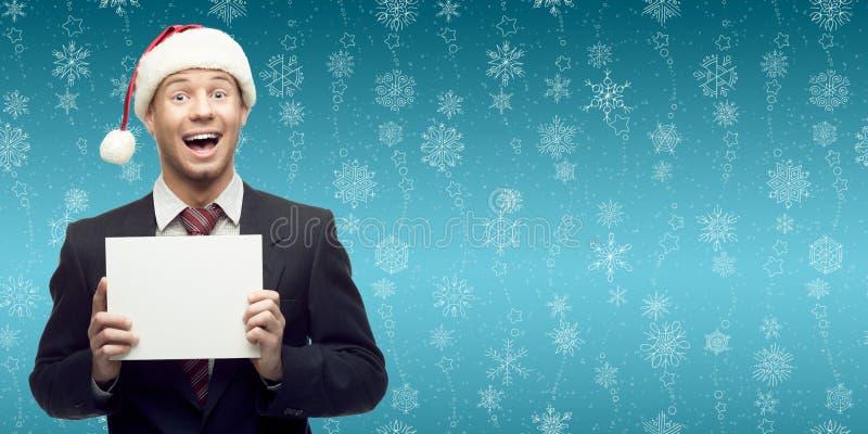 Νέο επιχειρησιακό άτομο στο σημάδι εκμετάλλευσης καπέλων santa πέρα από το χειμερινό backgro στοκ εικόνες