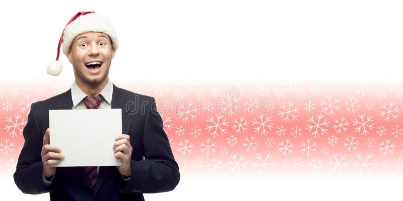 Νέο επιχειρησιακό άτομο στο σημάδι εκμετάλλευσης καπέλων santa πέρα από το χειμερινό backgro στοκ φωτογραφία με δικαίωμα ελεύθερης χρήσης
