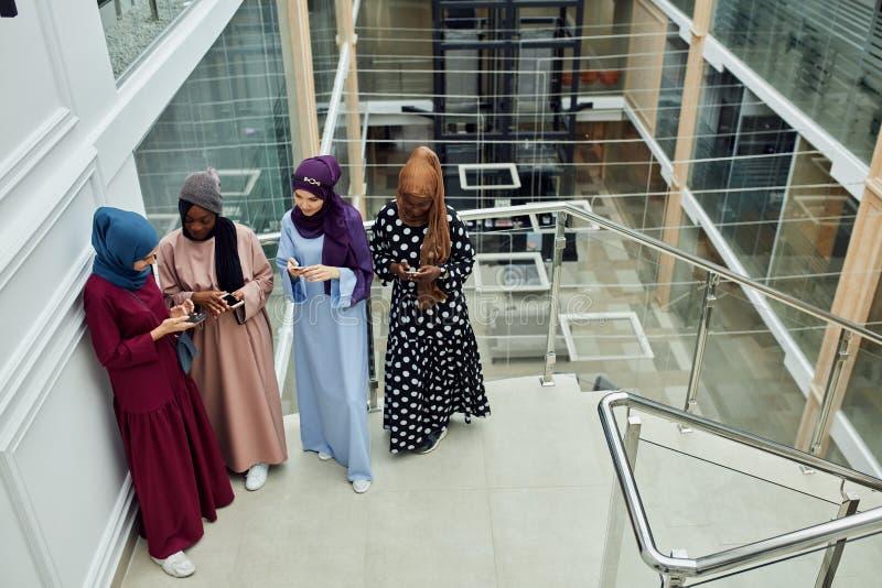 Νέο επιχειρησιακό μουσουλμανικό θηλυκό ζεύγους που χρησιμοποιεί την έξυπνη τηλεφωνική επαφή με το συνεργάτη στοκ εικόνα
