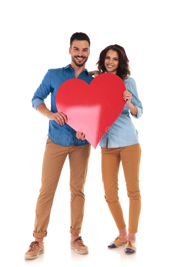 Νέο ερωτευμένο ζεύγος που κρατά τη μεγάλη κόκκινη καρδιά στοκ εικόνες