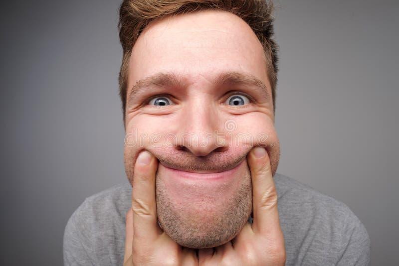 Νέο ευρωπαϊκό άτομο που κάνει ένα αστείο ευρύ χαμόγελο με τη βοήθεια των αντίχειρων του στοκ εικόνα