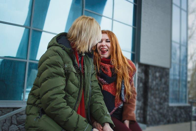 Νέο ευρωπαϊκό ζεύγος που έχει τη διασκέδαση στο χειμερινό αστικό υπόβαθρο Ύφος πανκ ή hipsters Το Redhead κορίτσι είναι ντυμένο σ στοκ φωτογραφία