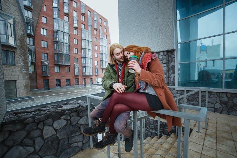 Νέο ευρωπαϊκό ζεύγος που έχει τη διασκέδαση στο χειμερινό αστικό υπόβαθρο Ύφος πανκ ή hipsters Το Redhead κορίτσι είναι ντυμένο σ στοκ φωτογραφία με δικαίωμα ελεύθερης χρήσης