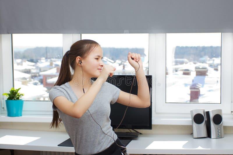 Νέο ευρωπαϊκό κορίτσι που ακούει τη μουσική και που χορεύει στο σπίτι στοκ εικόνα