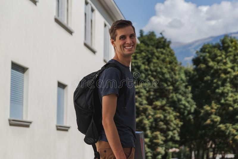 Νέο ευτυχές άτομο με το σακίδιο πλάτης που περπατά στο σχολείο μετά από τις καλοκαιρινές διακοπές στοκ φωτογραφία με δικαίωμα ελεύθερης χρήσης