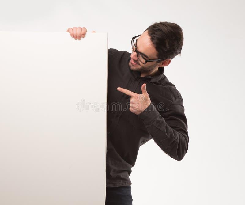 Νέο ευτυχές άτομο που παρουσιάζει παρουσίαση, που δείχνει στην αφίσσα πέρα από το γκρίζο υπόβαθρο στοκ φωτογραφία με δικαίωμα ελεύθερης χρήσης