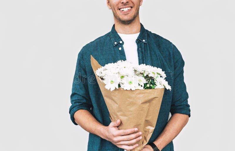 Νέο ευτυχές άτομο που χαμογελά και που παραδίδει μια ανθοδέσμη των άσπρων λουλουδιών καλλιεργημένος πυροβολισμός του όμορφου αρσε στοκ εικόνα με δικαίωμα ελεύθερης χρήσης