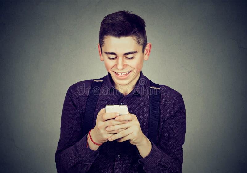 Νέο ευτυχές άτομο που χρησιμοποιεί ένα κινητό τηλεφωνικό χαμόγελο στοκ εικόνες