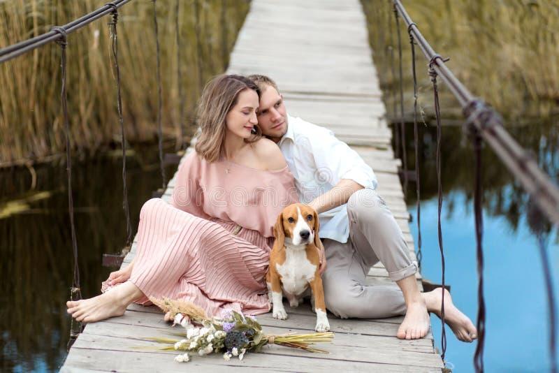 Νέο ευτυχές αγαπώντας ζεύγος που αγκαλιάζει στη γέφυρα πέρα από τον ποταμό Εδώ κοντά είναι το εσωτερικό σκυλί φυλής λαγωνικών του στοκ φωτογραφία