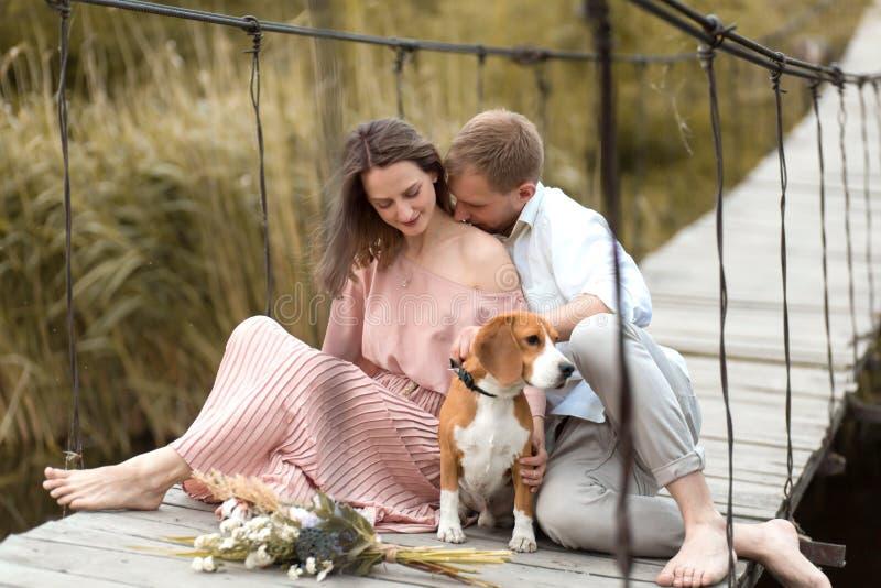 Νέο ευτυχές αγαπώντας ζεύγος που αγκαλιάζει στη γέφυρα πέρα από τον ποταμό Εδώ κοντά είναι το εσωτερικό σκυλί φυλής λαγωνικών του στοκ εικόνα