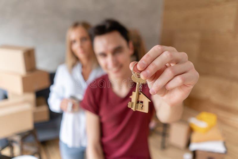 Νέο ευτυχές αγκάλιασμα ζευγών, που παρουσιάζει κλειδιά στο καινούργιο σπίτι Οικογενειακό ζεύγος που κινείται προς ένα νέο διαμέρι στοκ φωτογραφία με δικαίωμα ελεύθερης χρήσης