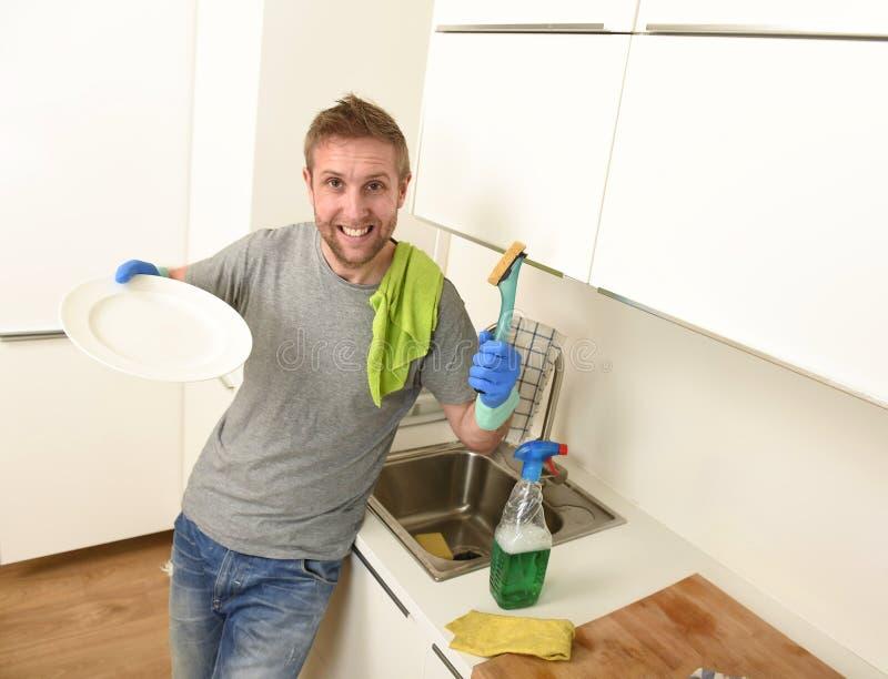 Νέο ευτυχές αξύριστο άτομο στα λαστιχένια γάντια πλύσης που κάνουν το χαμόγελο πιάτων βέβαιο και που χαλαρώνουν στοκ φωτογραφία με δικαίωμα ελεύθερης χρήσης