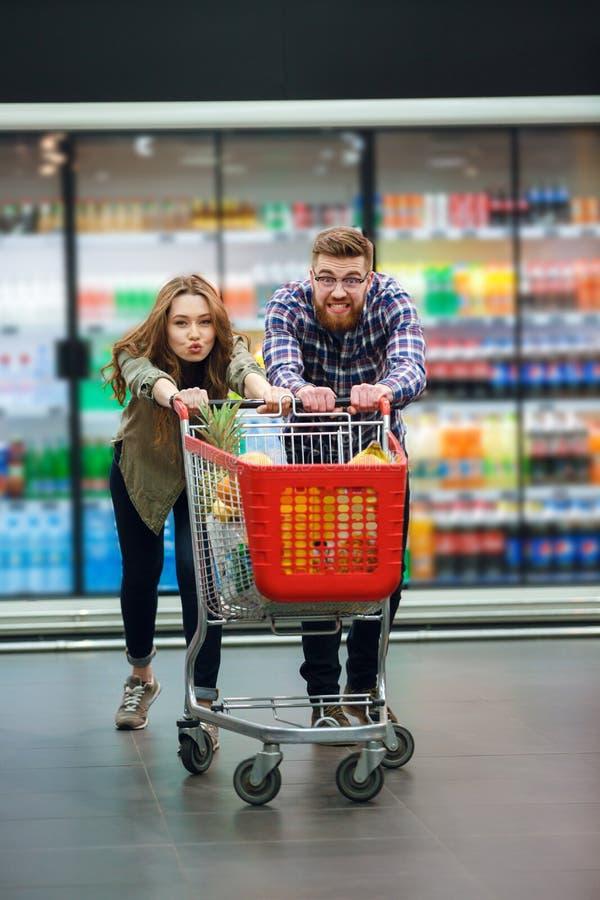 Νέο ευτυχές ζεύγος με το κάρρο τροφίμων που κάνει τις αγορές παντοπωλείων στοκ φωτογραφία με δικαίωμα ελεύθερης χρήσης