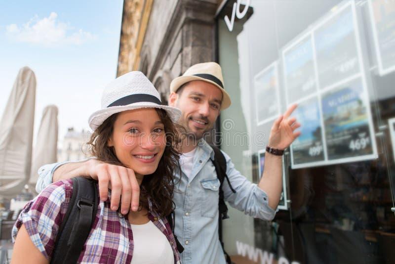 Νέο ευτυχές ζεύγος μπροστά από το ταξιδιωτικό γραφείο στοκ φωτογραφίες