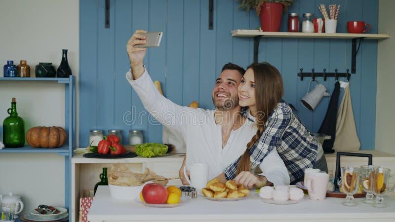 Νέο ευτυχές ζεύγος που παίρνει selfie το πορτρέτο ενώ έχοντας το πρόγευμα στην κουζίνα στο σπίτι στοκ εικόνα με δικαίωμα ελεύθερης χρήσης