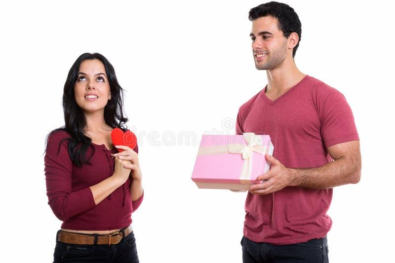 Νέο ευτυχές ζεύγος που χαμογελά με τον άνδρα που δίνει το κιβώτιο δώρων και το θόριο γυναικών στοκ φωτογραφία με δικαίωμα ελεύθερης χρήσης