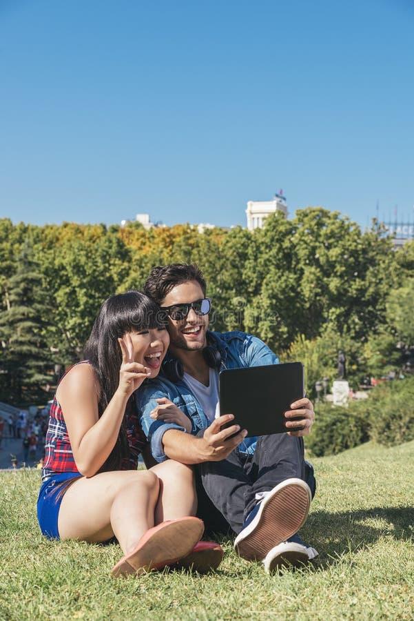 Νέο ευτυχές ζεύγος που χρησιμοποιεί την ταμπλέτα στο πάρκο στοκ φωτογραφία