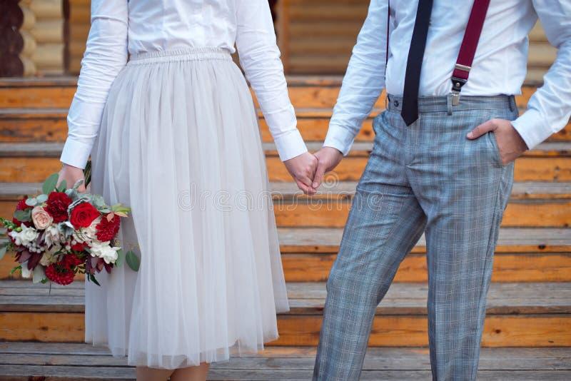 Νέο ευτυχές ζεύγος στα άσπρα πουκάμισα που έχουν μια ημερομηνία υπαίθρια στο δάσος ή το πάρκο με την ανθοδέσμη των τριαντάφυλλων στοκ εικόνα