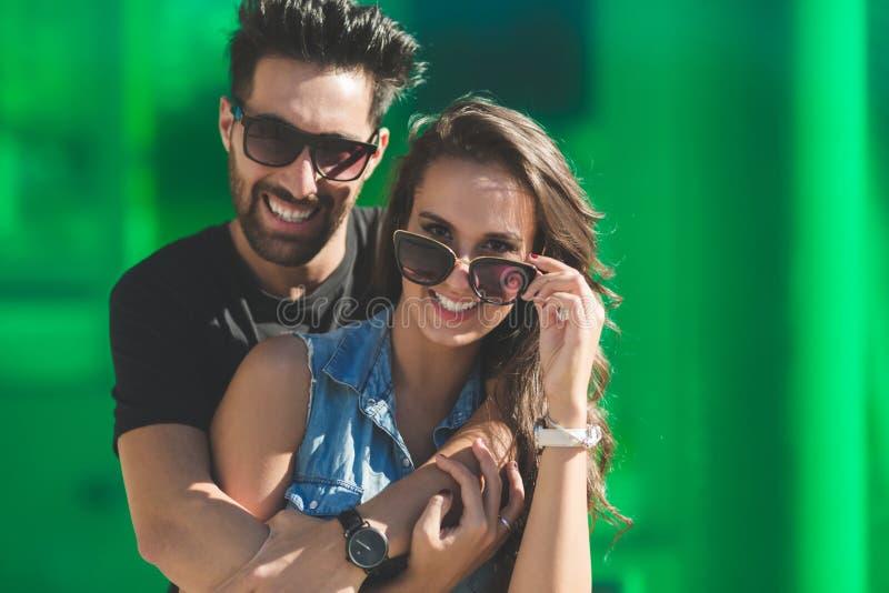 Νέο ευτυχές ζεύγος στα γυαλιά ηλίου που αγκαλιάζει το χαμόγελο στοκ εικόνα