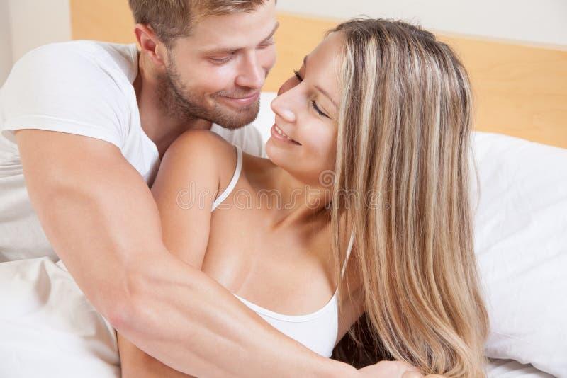 Νέο ευτυχές ζεύγος στο κρεβάτι στοκ εικόνες