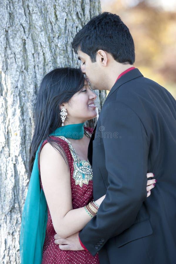 Νέο ευτυχές ινδικό άτομο που φιλά τη νύφη του στοκ φωτογραφία