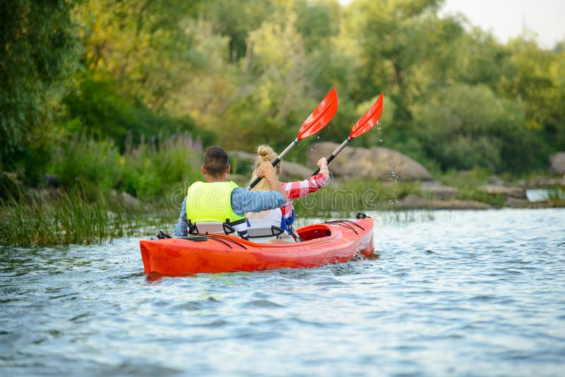 Νέο ευτυχές καγιάκ κωπηλασίας ζεύγους στον όμορφη ποταμό ή τη λίμνη στοκ εικόνα