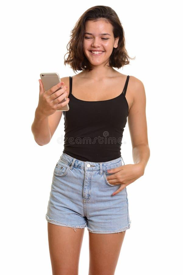 Νέο ευτυχές καυκάσιο έφηβη που χαμογελά και που κρατά το κινητό pH στοκ εικόνα
