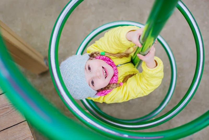 Νέο ευτυχές κορίτσι παιδιών που έχει τη διασκέδαση μια παιδική χαρά στοκ φωτογραφίες