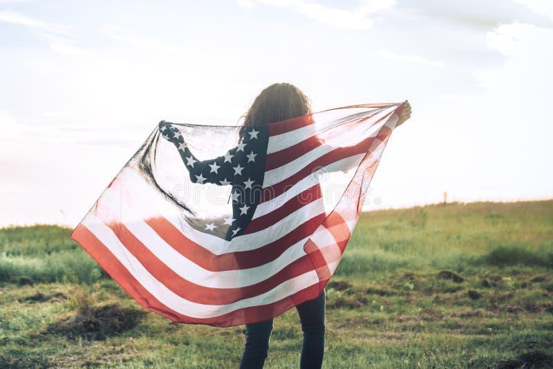 Νέο ευτυχές κορίτσι που τρέχει και που πηδά ξένοιαστο με τις ανοικτές αγκάλες πέρα από τον τομέα σίτου ΑΜΕΡΙΚΑΝΙΚΗ σημαία εκμετάλ στοκ εικόνα