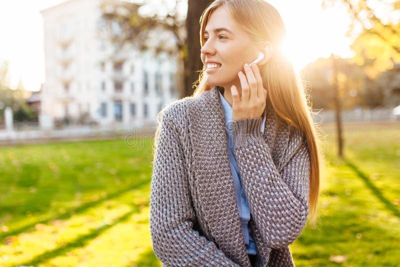 Νέο ευτυχές κορίτσι, σε μια καλή διάθεση, που ακούει τη μουσική με το wirele στοκ εικόνα