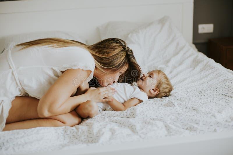 Νέο ευτυχές παιχνίδι μητέρων σε ένα άσπρο κρεβάτι που απολαμβάνει ένα ηλιόλουστο morni στοκ εικόνα