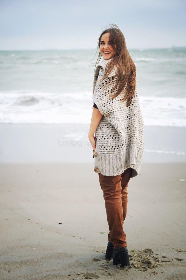 Νέο ευτυχές περιστασιακό γυναικών σε μια παραλία θάλασσας, φθινόπωρο υπαίθριο στοκ φωτογραφίες