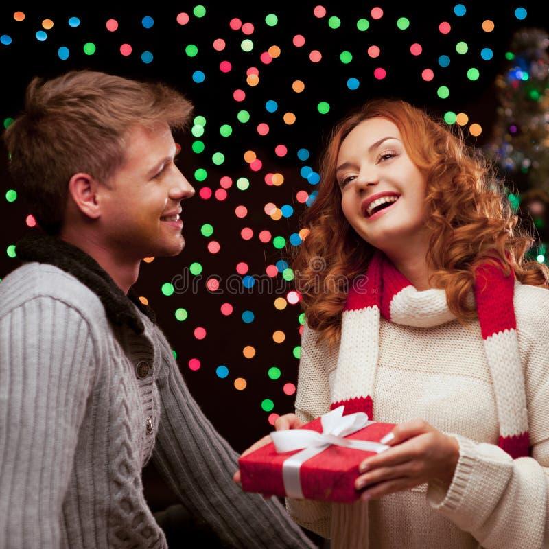 Νέο ευτυχές χαμογελώντας περιστασιακό ζεύγος που κάνει ένα παρόν στοκ φωτογραφία με δικαίωμα ελεύθερης χρήσης