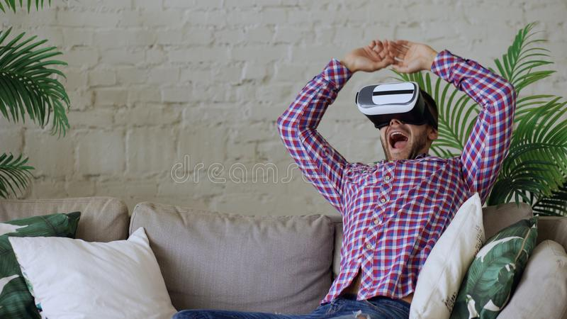 Νέο εύθυμο άτομο που φορά την κάσκα εικονικής πραγματικότητας που έχει την τηλεοπτική εμπειρία 360 VR καθμένος στον καναπέ στο κα στοκ εικόνα με δικαίωμα ελεύθερης χρήσης