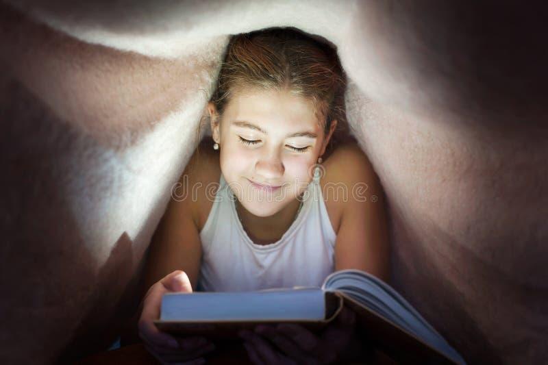 Νέο εύθυμο κρύψιμο έφηβη κάτω από το κάλυμμα και ανάγνωση του boo στοκ εικόνες