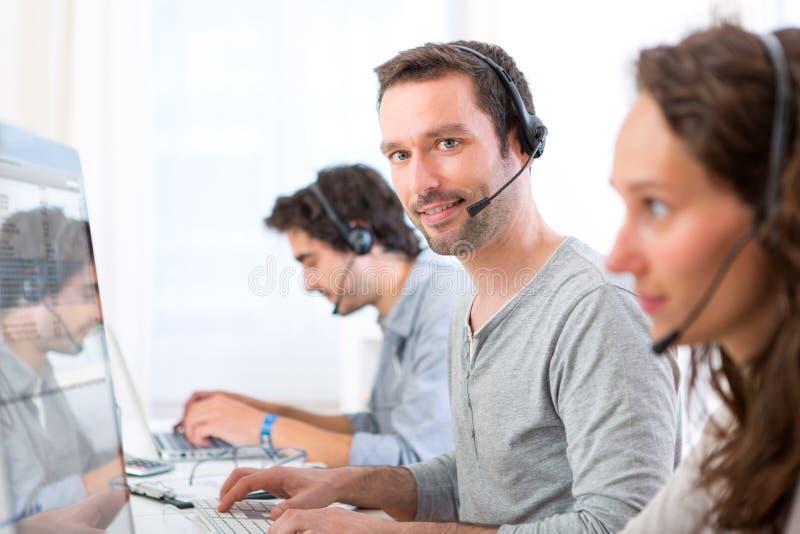 Νέο ελκυστικό άτομο που εργάζεται σε ένα τηλεφωνικό κέντρο στοκ εικόνα