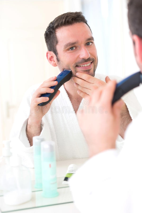 Νέο ελκυστικό άτομο που ξυρίζει τη γενειάδα του μπροστά από έναν καθρέφτη στοκ φωτογραφίες με δικαίωμα ελεύθερης χρήσης