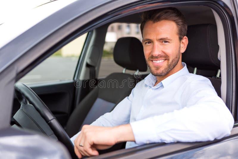Νέο ελκυστικό άτομο που οδηγεί το αυτοκίνητό του στοκ εικόνες