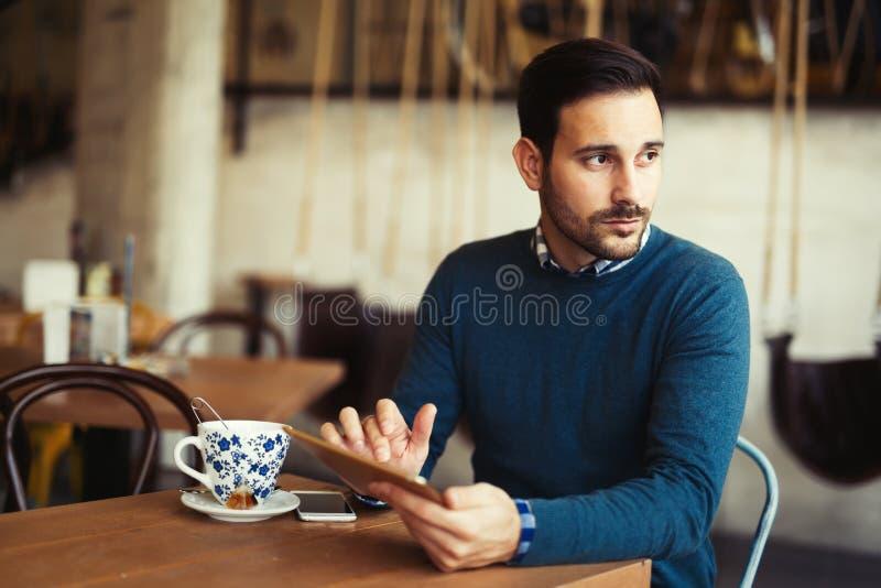 Νέο ελκυστικό άτομο που χρησιμοποιεί την ψηφιακή ταμπλέτα στη καφετερία στοκ εικόνες με δικαίωμα ελεύθερης χρήσης
