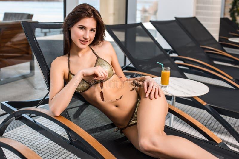 Νέο ελκυστικό λεπτό κορίτσι στη χαλάρωση μπικινιών στην καρέκλα γεφυρών wellness spa στο θέρετρο ξενοδοχείων στοκ εικόνα
