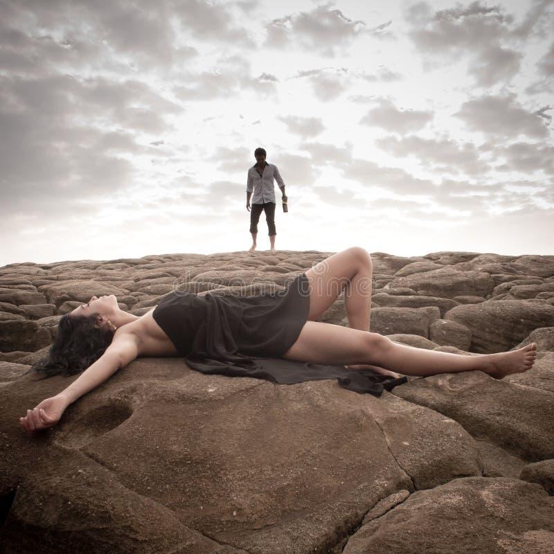 Νέο ελκυστικό ζεύγος που μοιράζεται μια στιγμή υπαίθρια στους βράχους παραλιών στοκ εικόνες με δικαίωμα ελεύθερης χρήσης