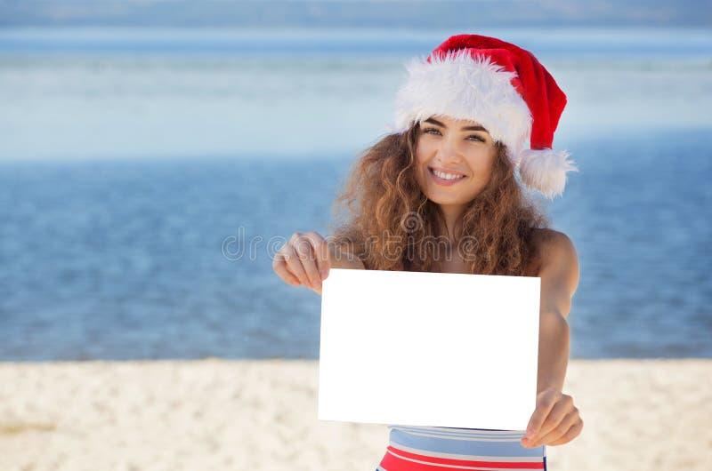 Νέο, ελκυστικό, σγουρό κορίτσι σε ένα κοστούμι λουσίματος και καπέλο Άγιου Βασίλη στην παραλία που κρατά ένα άσπρο φύλλο του εγγρ στοκ εικόνα με δικαίωμα ελεύθερης χρήσης