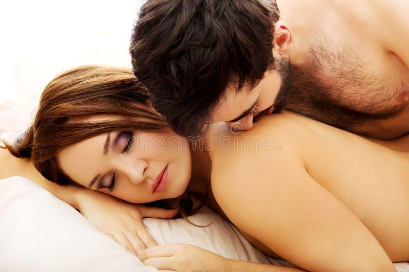 Νέο ζεύγος αγάπης στο κρεβάτι στοκ εικόνες