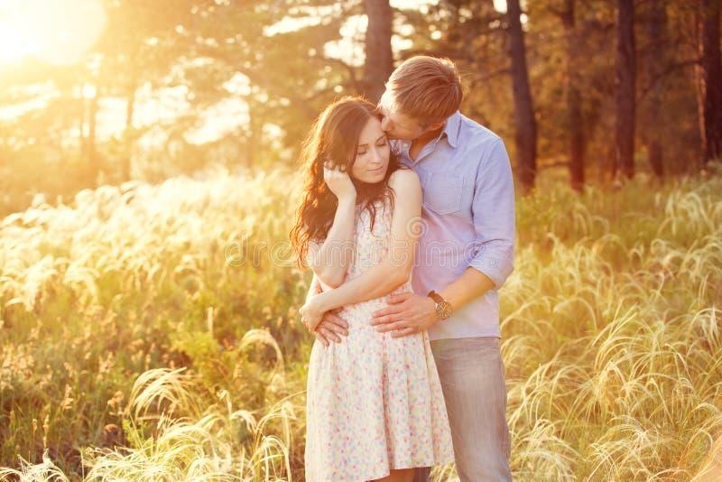 Νέο ζεύγος ερωτευμένο στο ηλιοβασίλεμα στον τομέα στοκ εικόνες με δικαίωμα ελεύθερης χρήσης