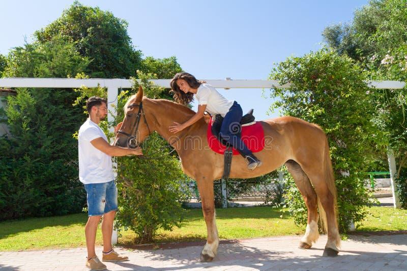 Νέο ζεύγος και το καφετής-ξανθό άλογό τους στοκ εικόνα