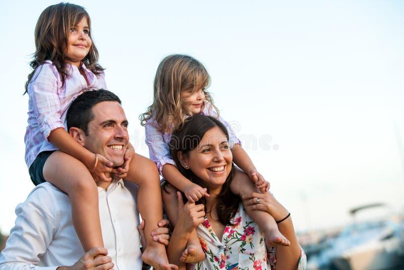 Νέο ζεύγος με τα παιδιά στους ώμους υπαίθρια στοκ φωτογραφίες