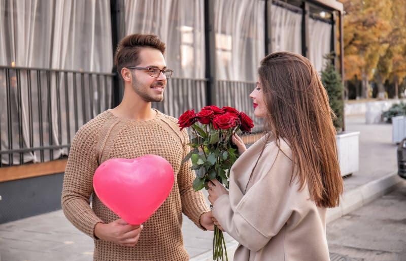 Νέο ζεύγος με την όμορφη ανθοδέσμη των τριαντάφυλλων υπαίθρια στοκ εικόνα