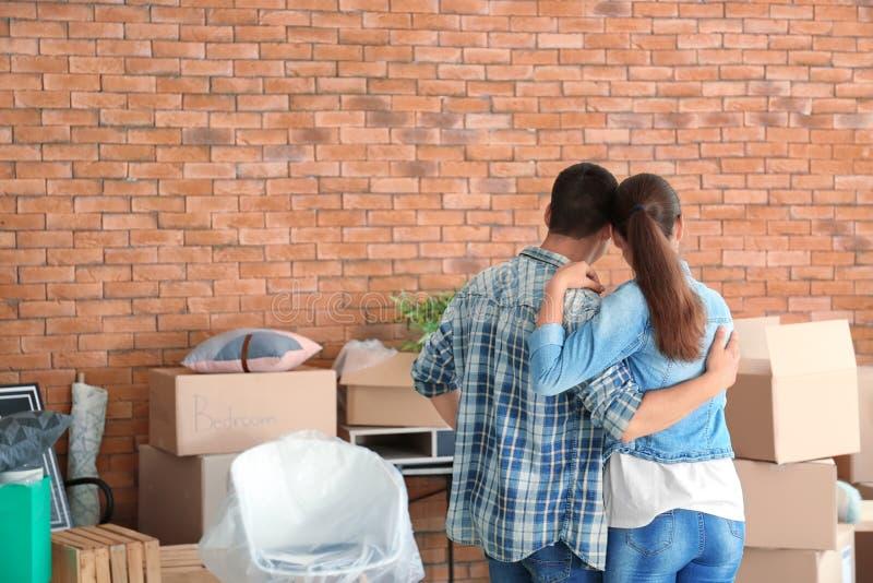 Νέο ζεύγος με τις περιουσίες στο εσωτερικό Κίνηση στο καινούργιο σπίτι στοκ φωτογραφίες